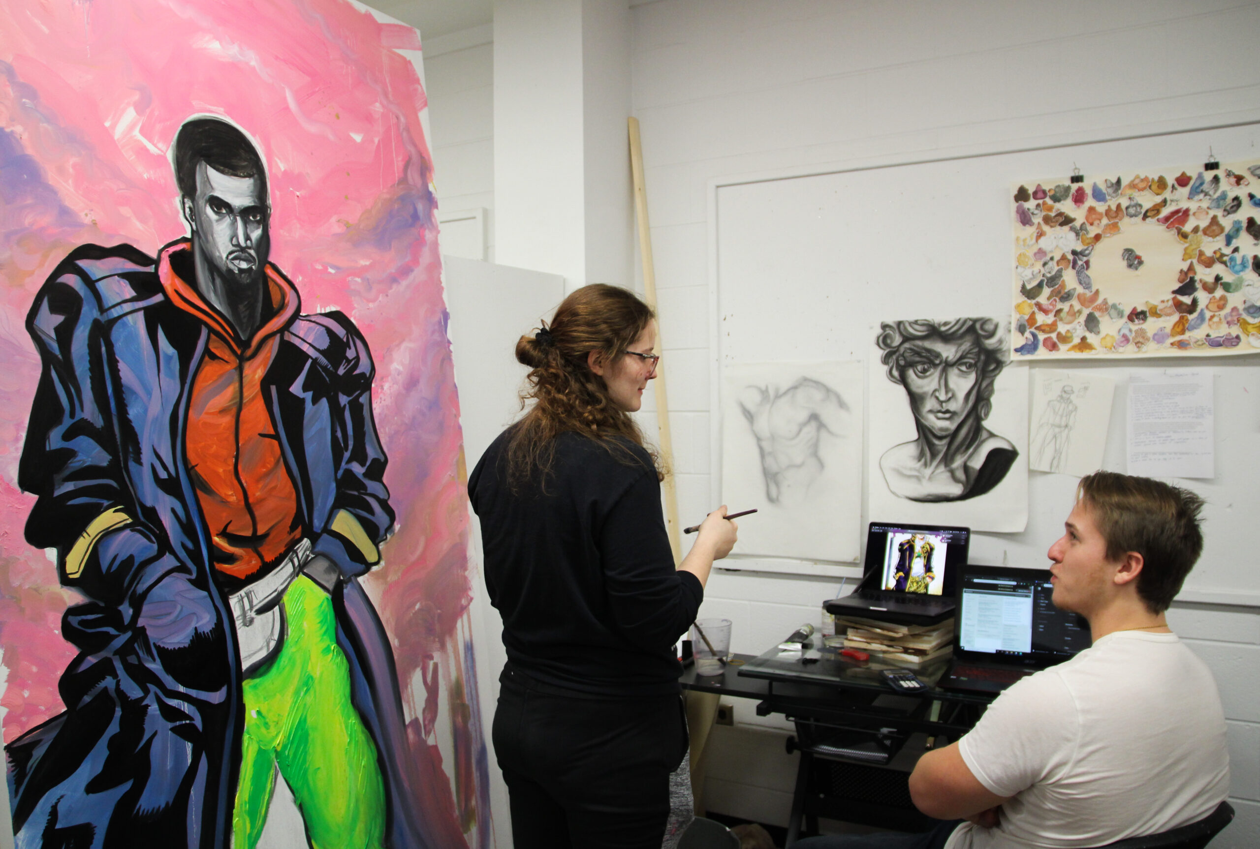 """Mady Ford and Mike Skibski, two University of Illinois students who met through the dating app """"OkCupid"""" in April, hangout in Ford's art studio as she works on her futuristic painting of Kanye West in Champaign, IL on Tuesday, Dec. 3, 2019."""